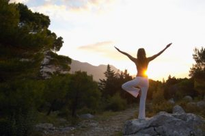 Young woman balancing on rock, practicing yoga pose, rear view