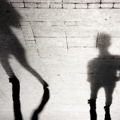 Upside down shadow of two person on city sidewalk in black and white
