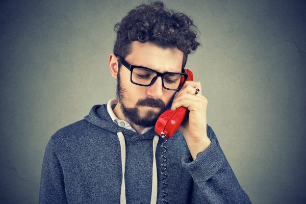 Young bearded man talking on telephone and looking unhappy with heart broken.
