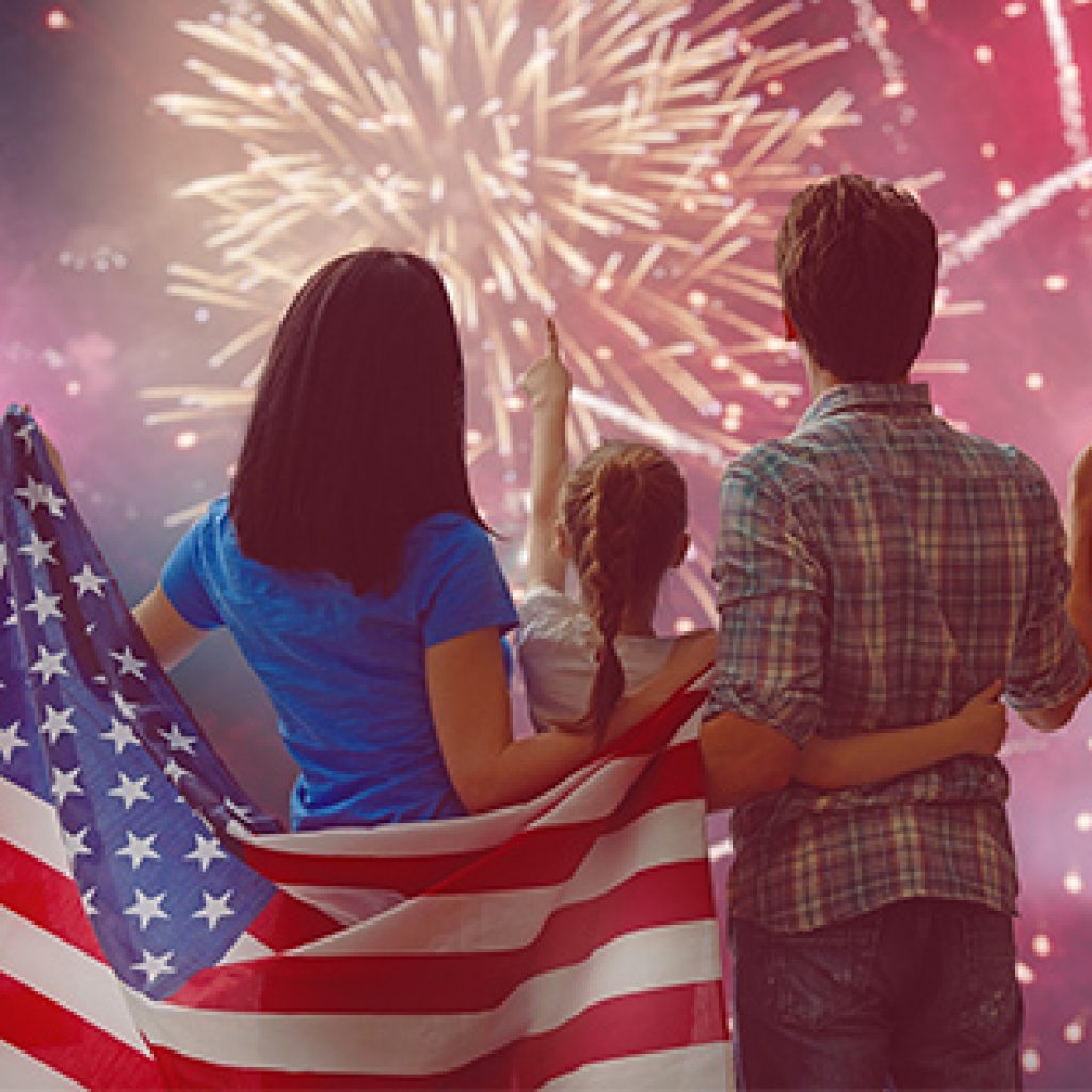Family watching fireworks holding american flag