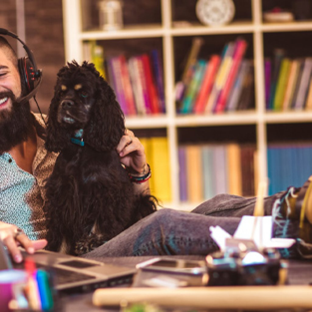 man and dog sitting in front of laptop