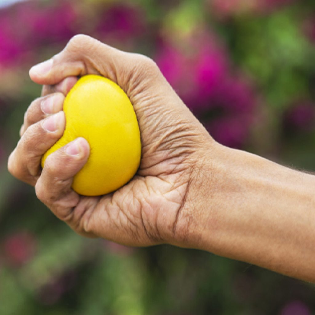 hand holding yellow stress ball
