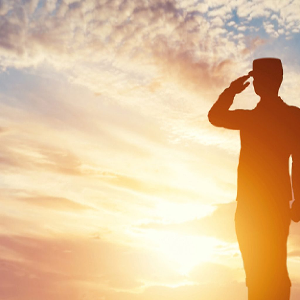 military man saluting in front of sunset