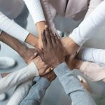 multi-ethnic hands coming together in a circle depicting Cultural Competency for Counselors & Professional Helpers