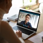 Young female sit at desk at home talk on video call with Indian colleague, woman have pleasant Webcam conference with biracial coworker, communicate online using wireless Internet connection