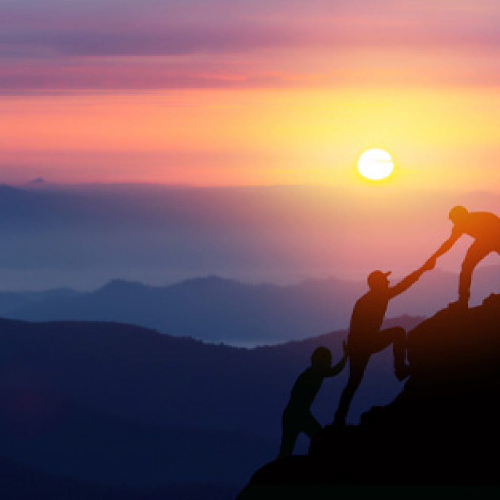 people helping one another climb a mountain